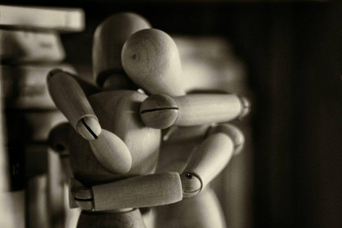 houten poppetjes omarmen elkaar